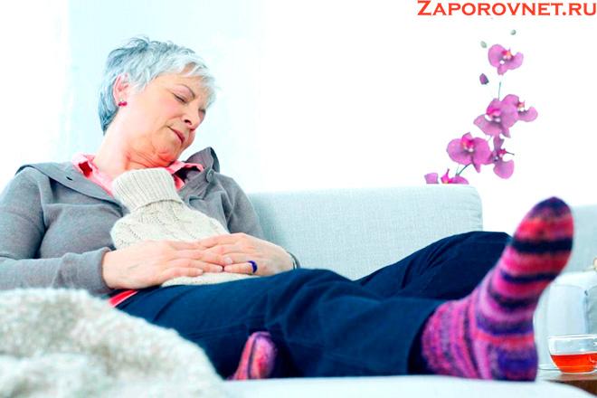 Пожилая женщина на диване с грелкой