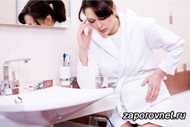 Беременная девушка сидит в ванной и держится за живот