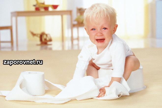 Ребенок сидит на горшке с туалетной бумагой
