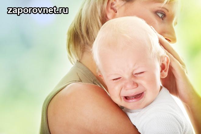 Мама держит на руках ребенка, который плачет